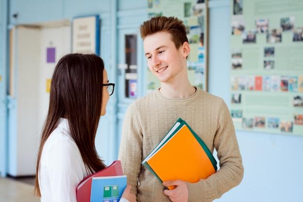 Studenten, die etwas besprechen und in der pause zwischen den kursen zeit miteinander haben