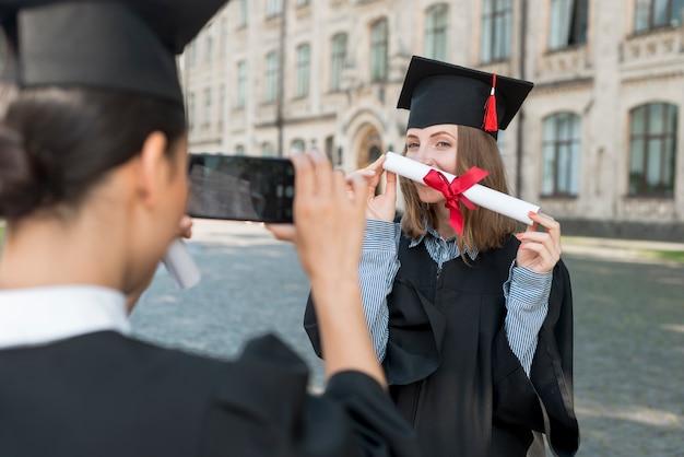 Studenten, die foto von einander an der staffelung machen