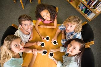 Studenten, die kaffeetassen auf tabelle halten