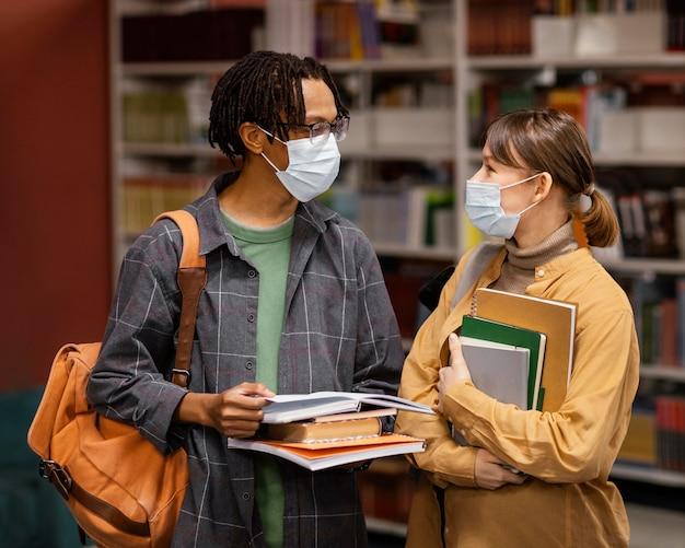 Studenten, die medizinische masken in der bibliothek tragen