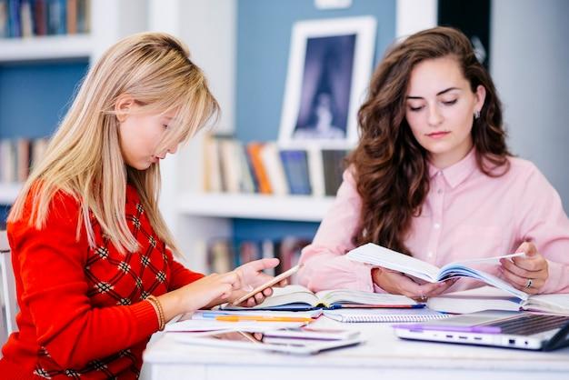 Studenten, die mit notizbüchern und telefon sitzen