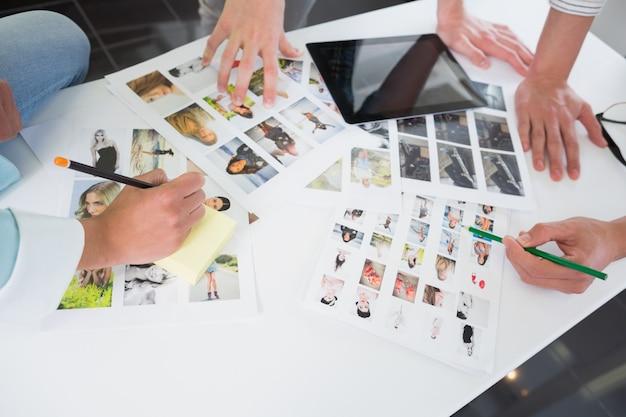 Studenten, die mit tabletten-pc und -fotos arbeiten