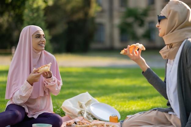 Studenten, die pizza essen. muslimische studenten essen pizza und reden nach dem unterricht, während sie auf gras sitzen sitting