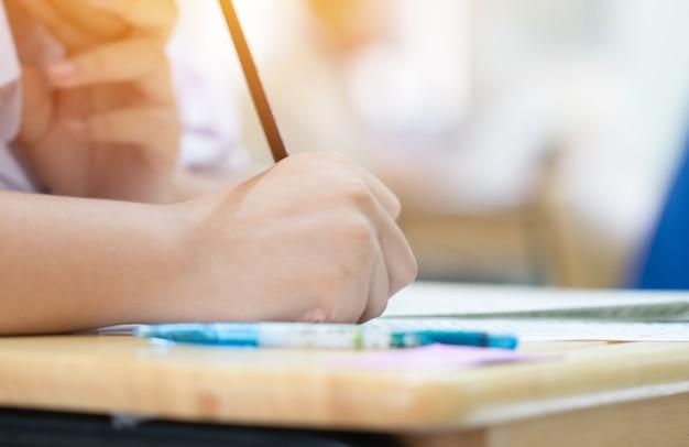 Studenten, die stift in den händen nehmen die prüfungen, prüfungsraum mit studenten schreibend halten