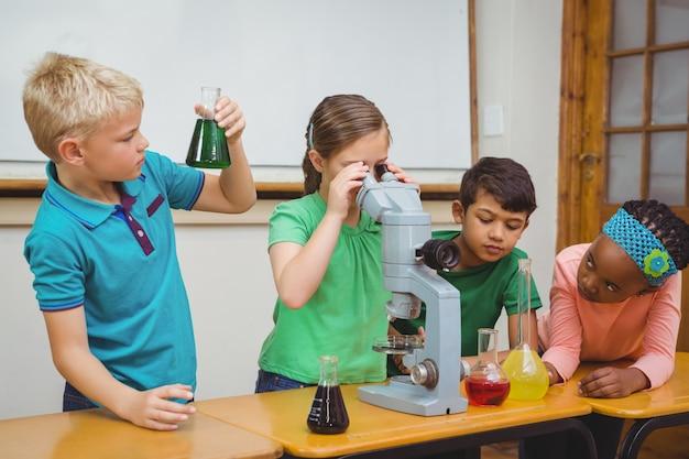 Studenten, die wissenschaftsbecher und ein mikroskop verwenden
