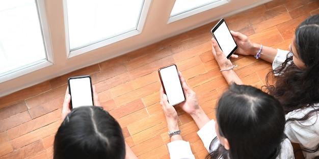 Studenten halten ein weißes smartphone mit leerem bildschirm in der hand, während sie auf einem holzboden im wohnzimmer liegen.