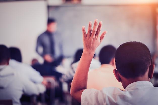 Studenten heben ihre hände, um lehrer zu fragen