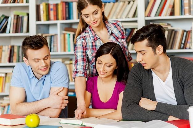 Studenten in der bibliothek. vier fröhliche studenten, die in einer bibliothek studieren