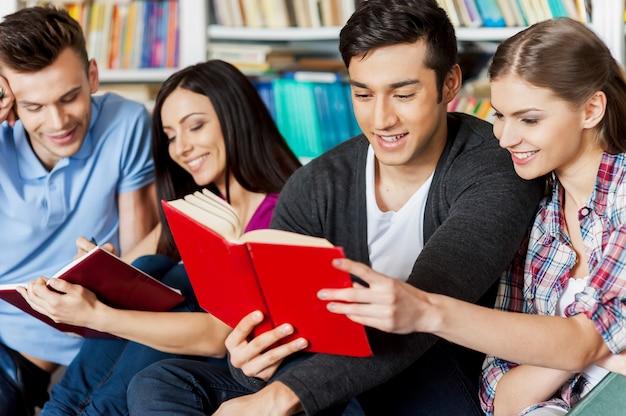 Studenten in der bibliothek. vier fröhliche studenten, die zusammen ein buch lesen, während sie in einer bibliothek gegen ein bücherregal sitzen