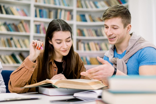 Studenten, kaukasischer hübscher junge und hübsches mädchen, die an einem tisch in einer bibliothek sitzen, während sie bücher lesen und zusammen lernen, ihre hausaufgaben oder prüfungsvorbereitung besprechen