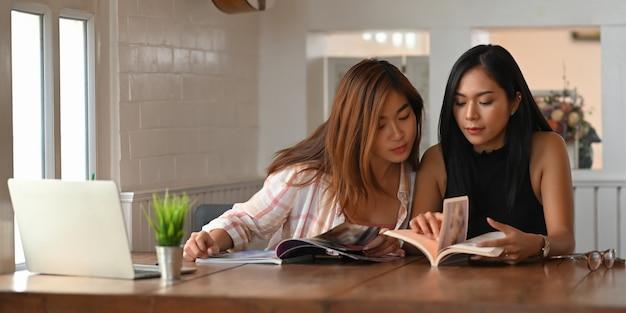 Studenten lesen ein buch, während sie zusammen im wohnzimmer sitzen.