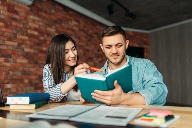 Studenten lesen gemeinsam lehrbuch. menschen mit buch bereiten sich auf prüfungen vor, gemeinsames projekt