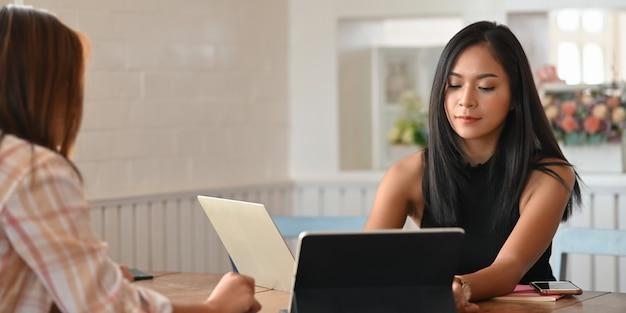 Studenten machen ihre hausaufgaben mit einem computer-laptop, während sie zusammen an einem hölzernen schreibtisch sitzen.
