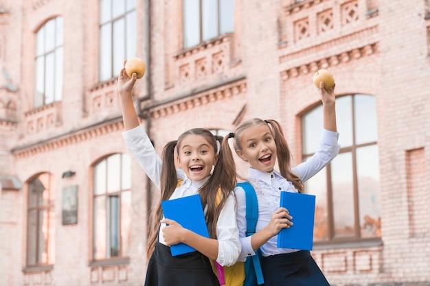 Studenten mädchen klassenkameraden mit rucksäcken beim mittagessen in der schule, kinderbetreuungskonzept.