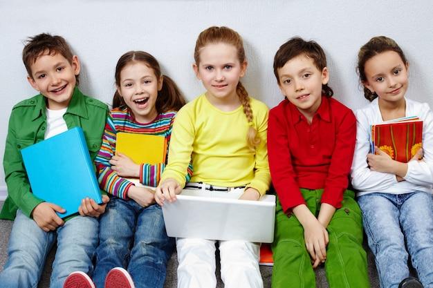Studenten mit bücher und laptop auf dem boden sitzen