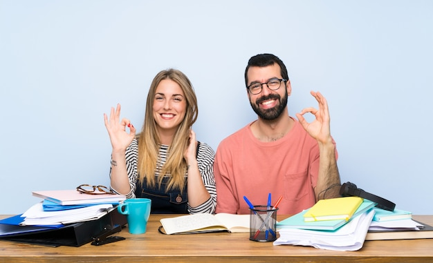 Studenten mit vielen büchern, die okayzeichen mit den fingern zeigen