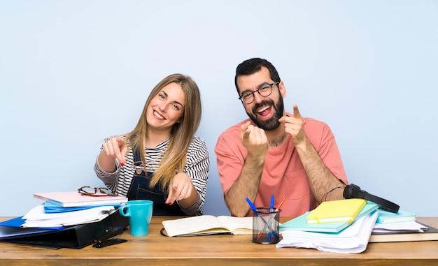 Studenten mit vielen büchern zeigen mit dem finger auf sie, während sie lächeln