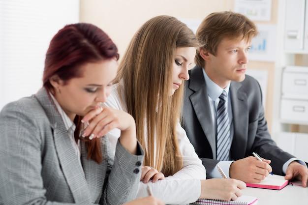 Studenten oder geschäftsleute schreiben während der konferenz etwas. geschäftstreffen, blogging oder berufsbildungskonzept