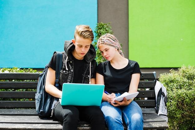 Studenten posieren auf bank mit laptop