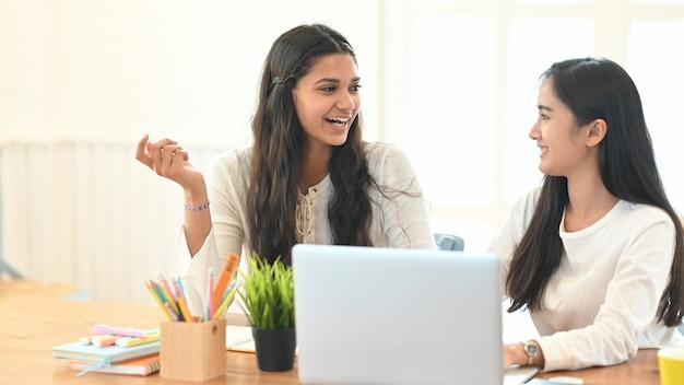 Studenten sitzen zusammen vor einem computer-laptop am schreibtisch.