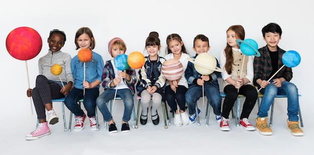 Studenten sitzt planet spielzeug halten.