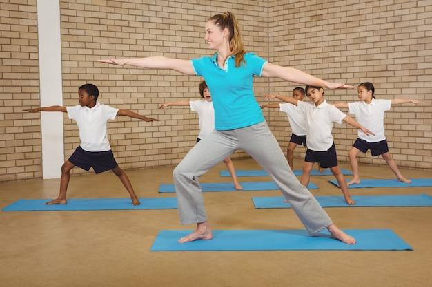 Studenten und lehrer, die yogahaltung tun