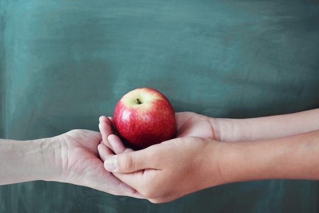 Studenten- und lehrerhände, die roten apfel mit tafelhintergrund halten