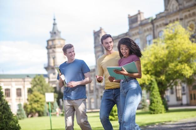 Studenten. zwei jungs und ein mädchen gehen spazieren und diskutieren über zukünftige prüfungen
