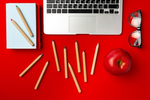 Studentenarbeitsplatz mit offenem laptop und rotem apfel, andere lieferungen