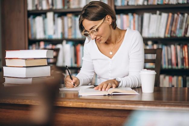 Studentenfrau, die an der bibliothek studiert und kaffee trinkt