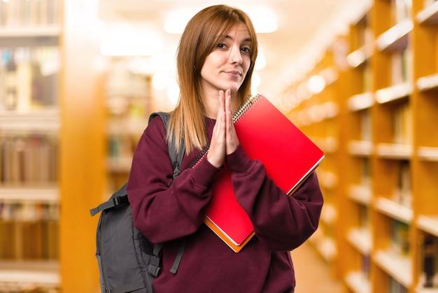 Studentenfrau, die auf unfocused hintergrund plädiert. zurück zur schule