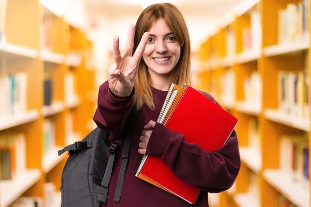 Studentenfrau, die drei auf unfocused hintergrund zählt. zurück zur schule