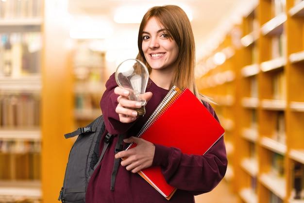 Studentenfrau, die eine birne auf unfocused hintergrund hält. zurück zur schule