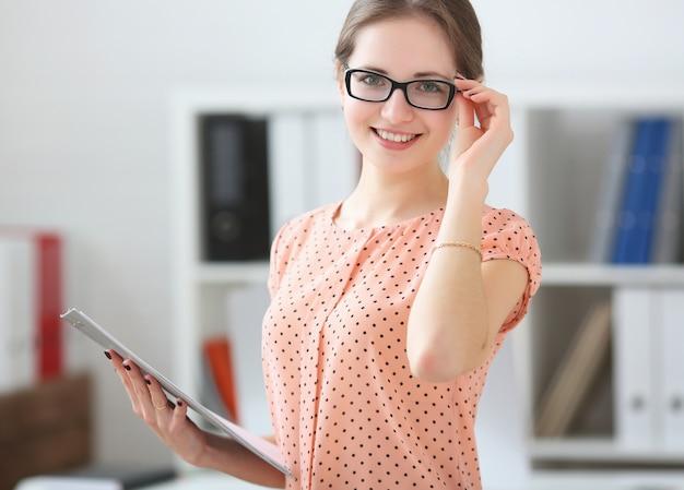 Studentenfrau, die eine tablette für anmerkungen in den händen im publikum hält