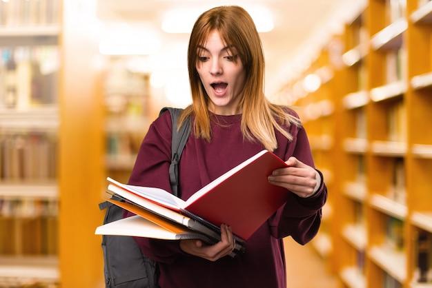 Studentenfrauen-lesebuch auf unfocused hintergrund. zurück zur schule