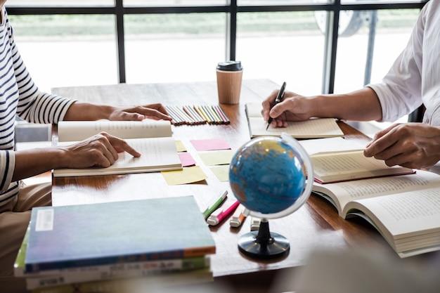 Studentengruppe, die am schreibtisch in der bibliothek sitzt und studiert und liest, hausaufgaben macht und unterrichtspraxis macht