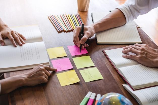 Studentengruppe, die am schreibtisch in der bibliothek sitzt und studiert und liest, hausaufgaben und lektionen macht