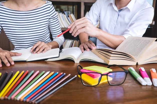 Studentengruppe, die am schreibtisch in der bibliothek studiert und liest, hausaufgaben und unterrichtspraxis tut