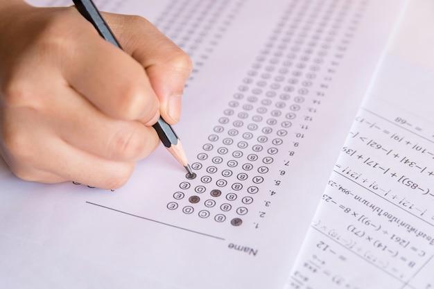 Studentenhand, die ausgewählte auswahl des bleistiftschreibens auf antwortblättern hält