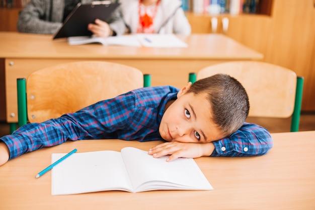 Studentenjunge, der auf schreibtisch im klassenzimmer sich lehnt