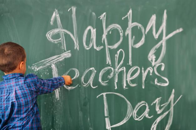 Studentenjunge, der glücklichen lehrertag auf tafel schreibt