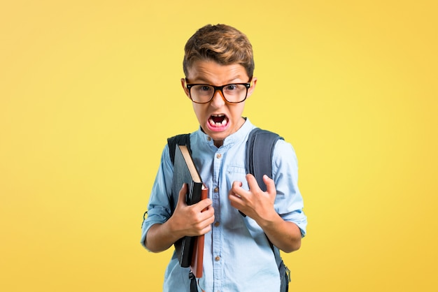 Studentenjunge mit dem rucksack und gläser verärgert verärgert in der wütenden geste. zurück zur schule