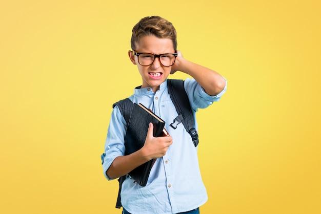 Studentenjunge mit dem rucksack und gläsern, die beide ohren mit den händen bedecken. zurück zur schule
