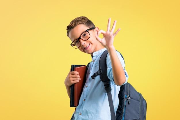 Studentenjunge mit dem rucksack und gläsern, die ein okayzeichen mit den fingern zeigen. zurück zur schule