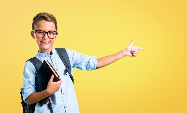 Studentenjunge mit dem rucksack und gläsern, die finger auf die seite zeigen. zurück zur schule