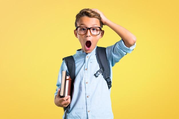 Studentenjunge mit dem rucksack und gläsern unglücklich und mit etwas frustriert.