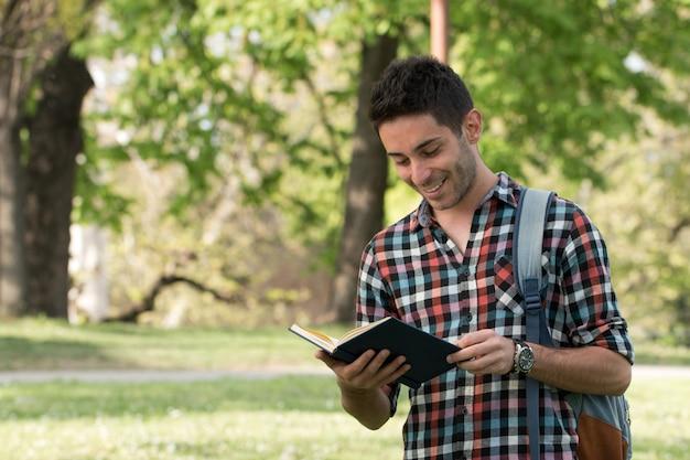 Studentenkerl, der hausarbeit im park tut.