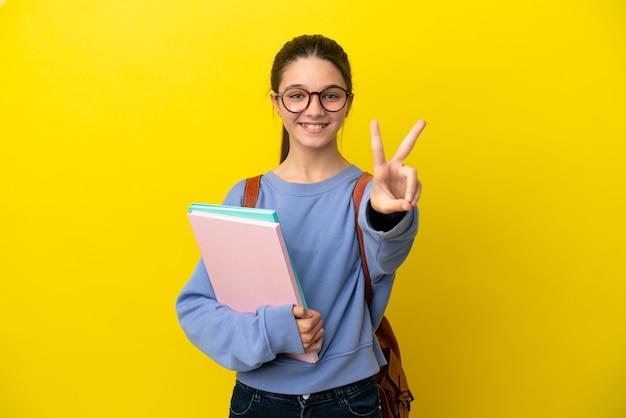 Studentenkindfrau über isolierter gelber oberfläche lächelt und zeigt victory-zeichen