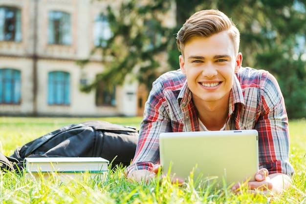Studentenleben genießen. hübscher junger mann, der an digitaler tablette arbeitet und lächelt, während er auf gras liegt