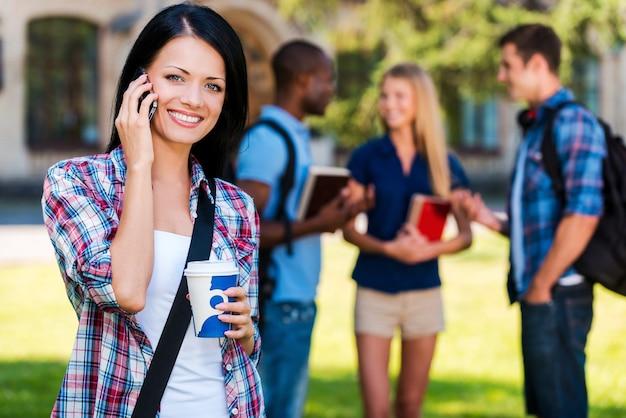 Studentenleben genießen. schöne junge frau, die mit dem handy spricht und lächelt, während sie gegen das universitätsgebäude steht, während ihre freunde im hintergrund plaudern